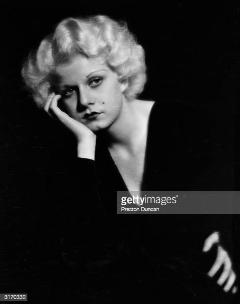 American actress Jean Harlow wearing a dark dress with a lowcut neckline