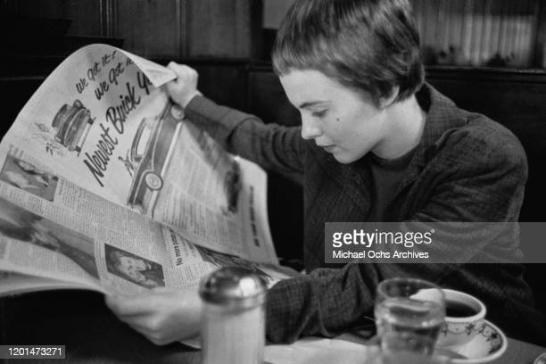 American actress Jean Seberg reading a newspaper in her home town of Marshalltown, Iowa, March 1957. She has just returned to the USA after shooting...