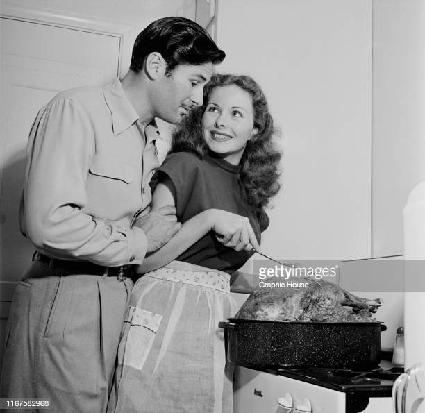 American actress Jeanne Crain and her husband Paul Brinkman cooking a large turkey at home, circa 1955.