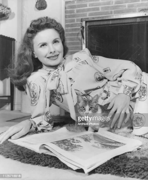 American actress Jeanne Crain at home with a pet cat circa 1955