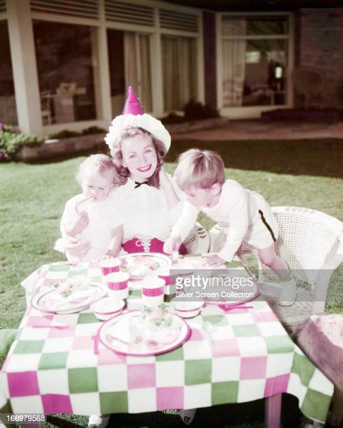 American actress Jeanne Crain wearing a party hat at an outdoor meal with two children circa 1950