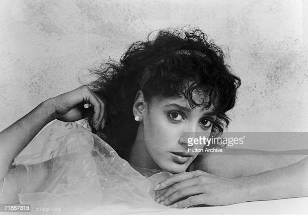 American actress Jennifer Beals holding a sheer shawl up to her chin 1983