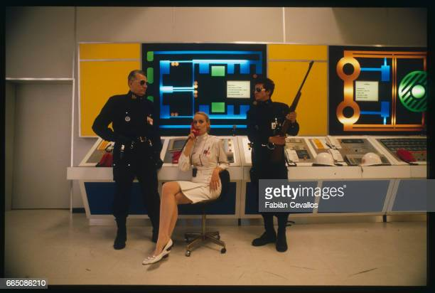 American actress Jerry Hall sits on a chair before a control desk phoning, between two armed security guards, on the set of the Italian movie Topo...
