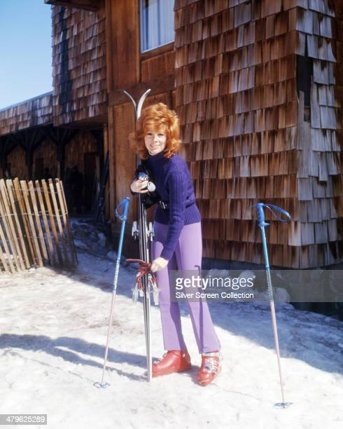 American actress Jill St John holding a pair of skis at a winter resort circa 1970