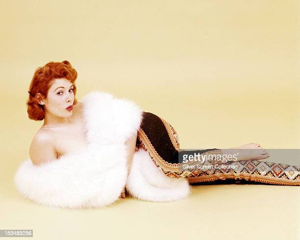 American actress Jill St John reclining in matador trousers and a fur stole circa 1960