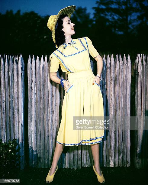American actress Joan Bennett in a yellow sun dress with blue and purple trim and a matching sun hat circa 1935