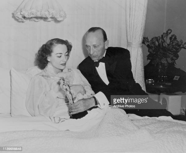 American actress Joan Crawford accepts her Academy Award for Best Actress for the film 'Mildred Pierce' from the film's director Michael Curtiz...