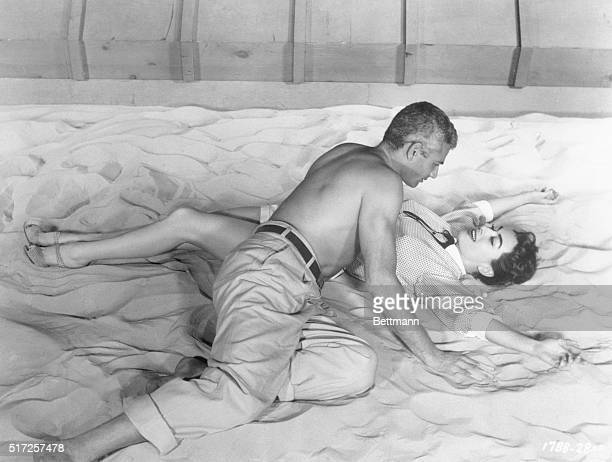 American actress Joan Crawford and Jeff Chandler act out a scene from the movie Female on the Beach while lying on the sand together.