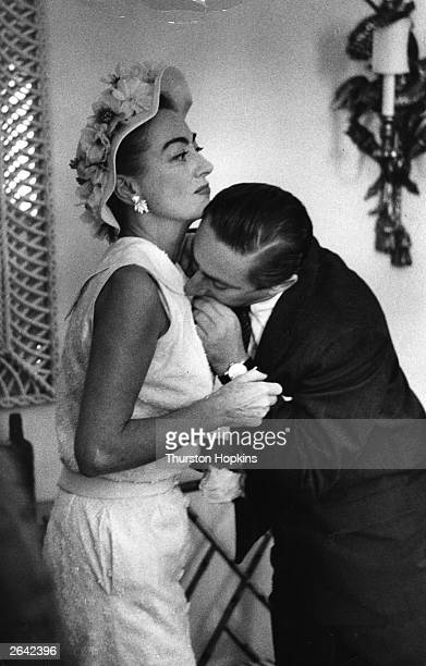 American actress Joan Crawford asks her assistant to bite off a loose thread from her dress at the Dorchester Hotel London 1st July 1956 Original...