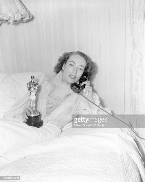 American actress Joan Crawford holding her Academy Award for Best Actress for her performance in 'Mildred Pierce' as she makes a telephone call from...