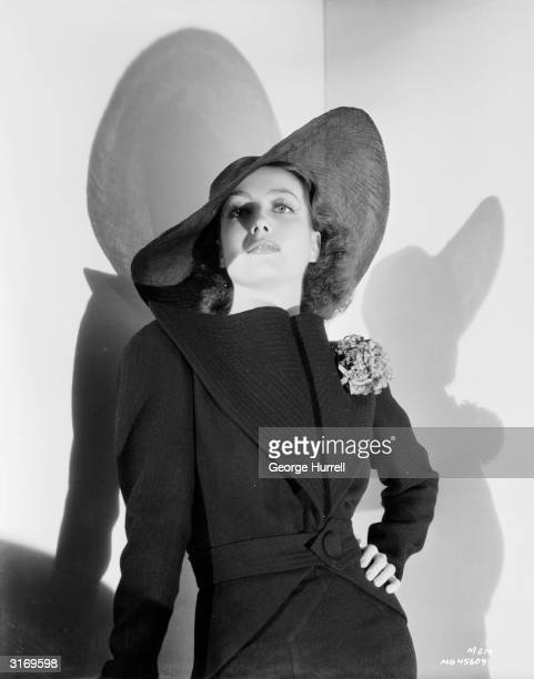 American actress Joan Crawford wearing a belted coat with a broad collar