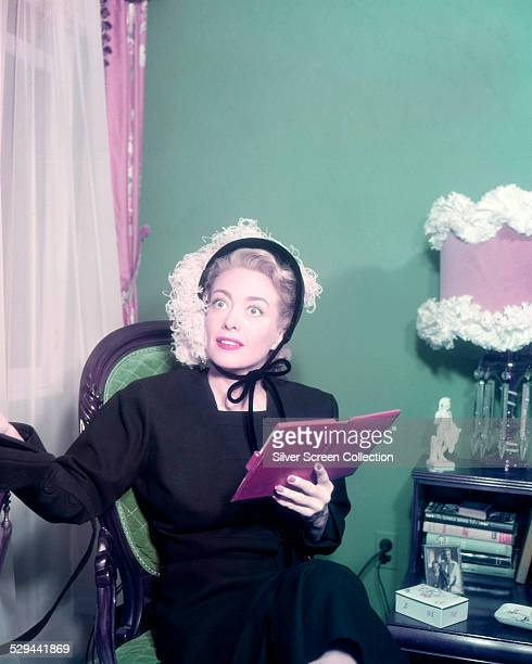 American actress Joan Crawford wearing a bonnet decorated with ostrich feather and holding a diary circa 1950