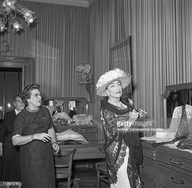American actress Joan Crawford wearing a hat with veil a necklace earrings and a brooch standing in front of a mirror smoking a cigarette and trying...