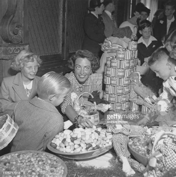 American actress Joan Crawford with her adopted children Christina and Christopher at a children's Easter party in Hollywood California 1949