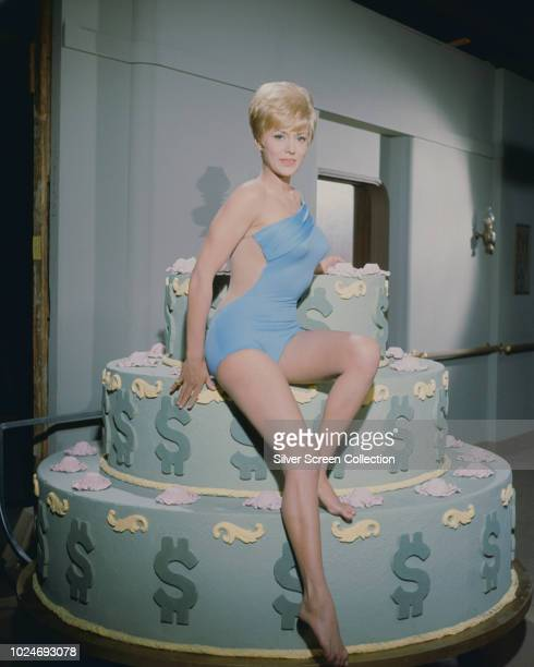 American actress Julie Gregg sitting on a large layered cake decorated with dollar signs circa 1965