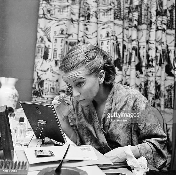 American actress Julie Harris curls her eyelashes as she prepares to play the role of Sally Bowles in the Broadway drama 'I Am a Camera,' written and...