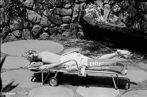 American actress Julie Newmar covered only in a towel sunbathes in a scene from the film 'The MarriageGoRound' Los Angeles California 1960