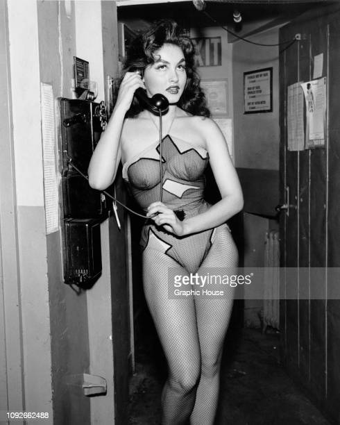 American actress Julie Newmar makes a phone call during a Broadway stage production of 'Li'l Abner' in New York City, 1956. She is playing Stupefyin'...