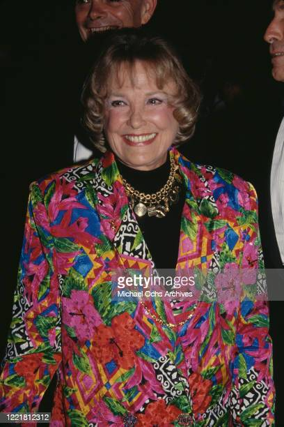 American actress June Allyson wearing multicoloured patterned jacket with a gold necklace from which hangs a variety of pendants smiling at an...