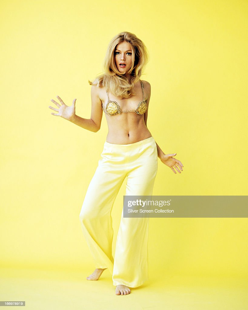 American actress Karen Jensen dancing in a yellow bra top and yellow trousers, circa 1970.