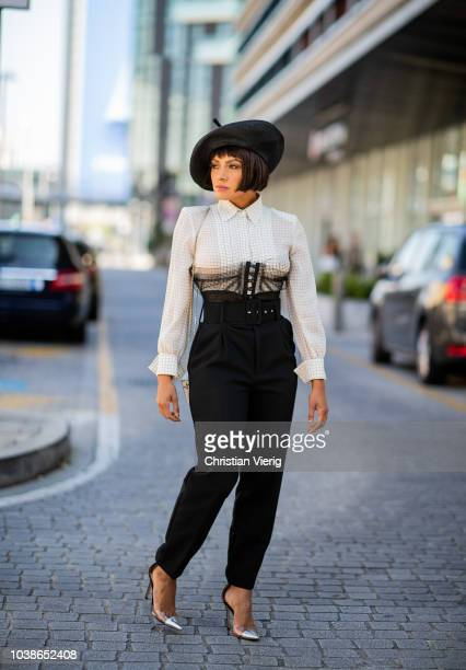 American actress Kat Graham is seen wearing black hat white button shirt high waist pants white mini bag all Jean Paul Gaultier during Milan Fashion...