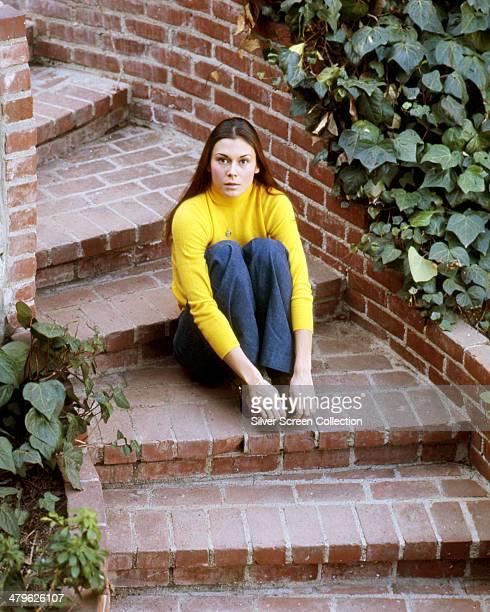 American actress Kate Jackson sitting on a flight of garden steps circa 1973