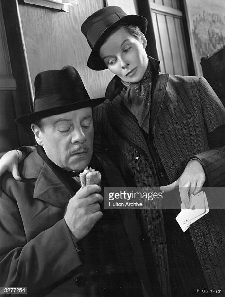 American actress Katharine Hepburn masquerades as a boy and with her arm round the shoulder of English actor Edmund Gwenn accuses him of cheating at...