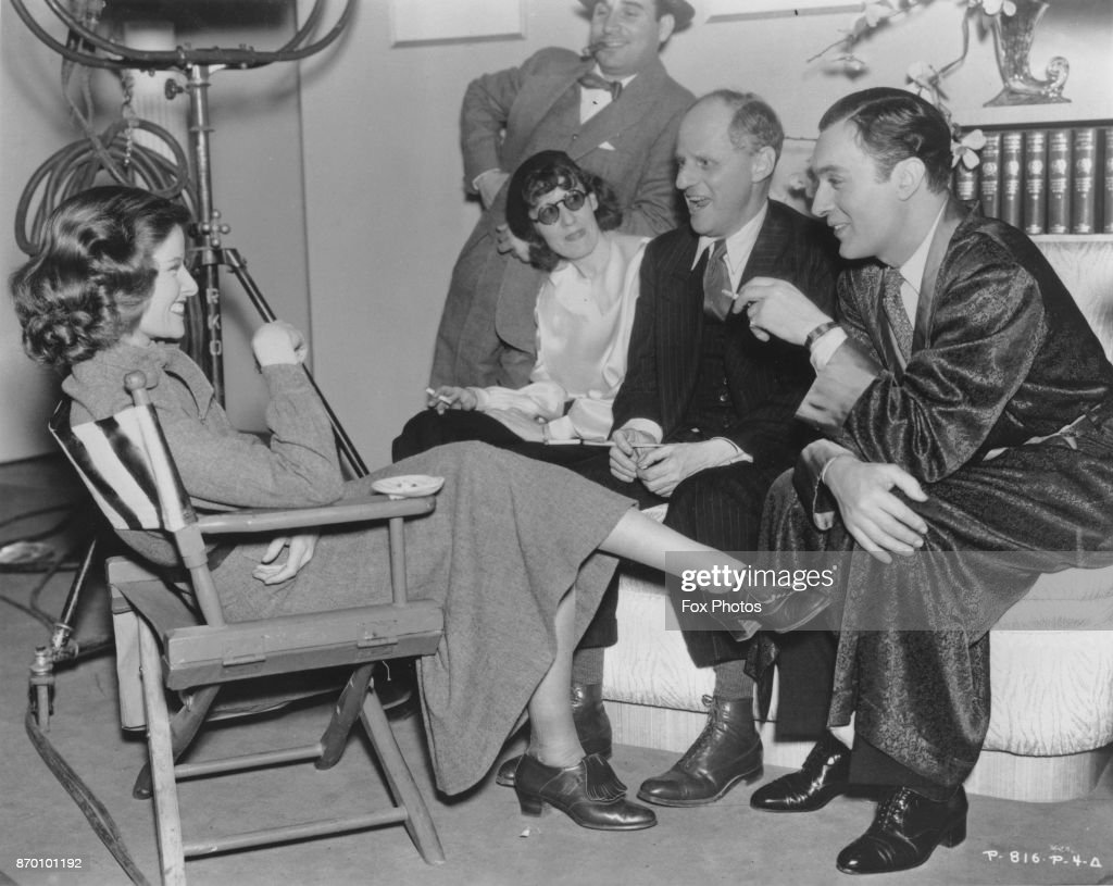 American actress Katharine Hepburn (1907 - 2003) on the set of the film 'Break of Hearts' with co-star Charles Boyer (in robe) and director Philip Moeller (next to Boyer), 1935.