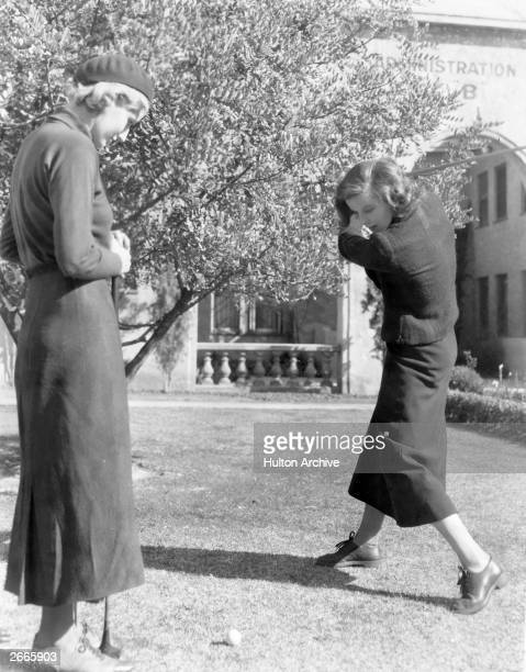 American actress Katharine Hepburn plays a game of golf with a friend