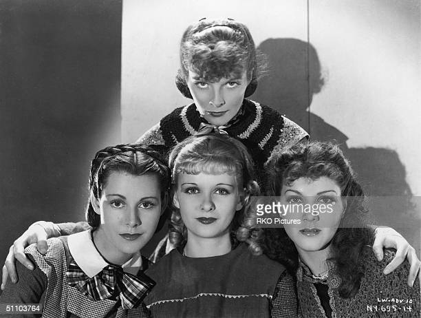 American actress Katharine Hepburn stands behind costars Frances Dee Joan Bennett and Jean Parker as they pose for a publicity portrait to promote...