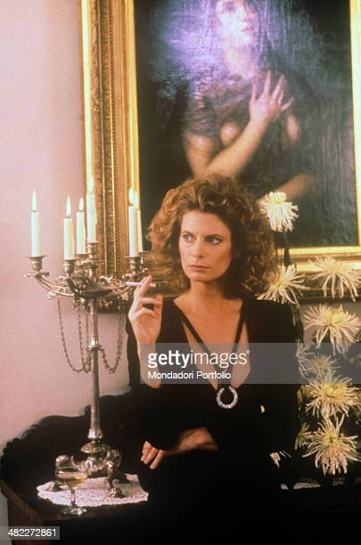 American actress Kathryn Harrold smoking a cigarette in front of a painting portraying Mary Magdalene in the film Raw Deal 1986
