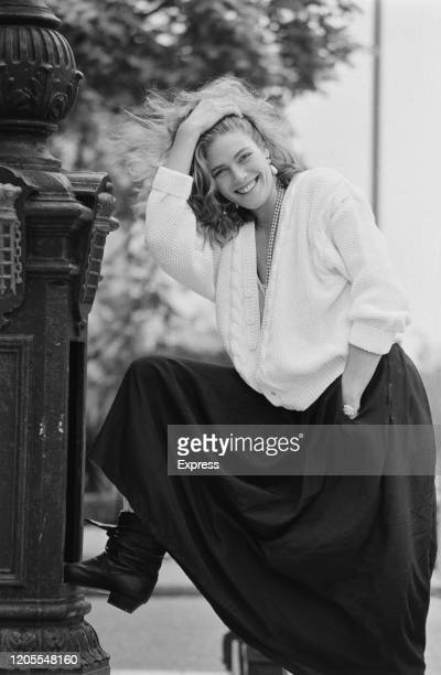 American actress Kelly McGillis wearing a pearl necklace with a white cardigan and long dark skirt smiles with her hand on her head and her foot...