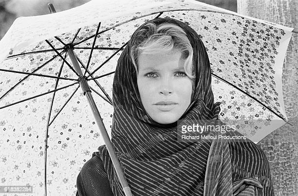 American actress Kim Basinger holds an umbrella on the set of the 1983 James Bond film Never Say Never Again directed by Irvin Kershner and starring...