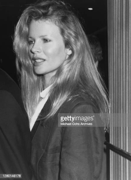 American actress Kim Basinger, with shoulder-length blonde hair, wearing a black jacket over a white top, circa 1987.