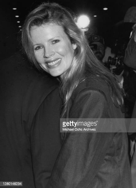 American actress Kim Basinger, with shoulder-length blonde hair, wearing a black jacket, smiles with her head resting on an unidentified shoulder,...
