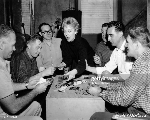 American actress Kim Novak gambles with crew members on the set of a Columbia Pictures film circa 1955