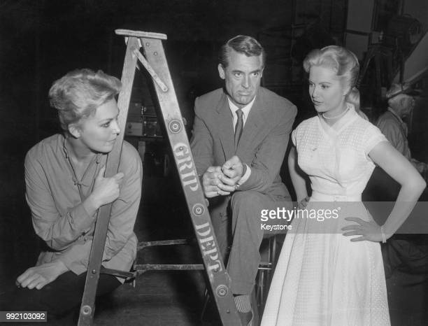 American actress Kim Novak visits actors Cary Grant and Martha Hyer on the set of the film 'Houseboat' 1958