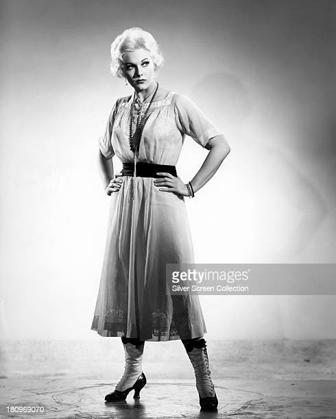 American actress Kim Novak wearing a kneelength dress and boots circa 1955