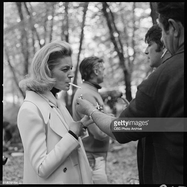 American actress Lauren Bacall has her cigarette lighted for her during an offcamera moment during the filming of the CBS special 'The Paris...