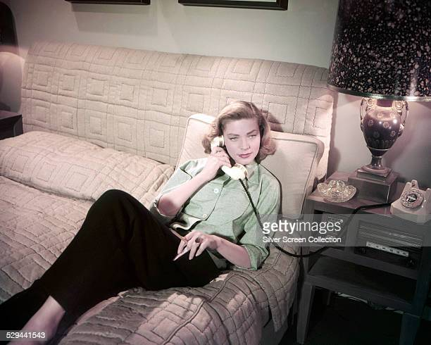 American actress Lauren Bacall lying on a bed and making a telephone call, circa 1955.