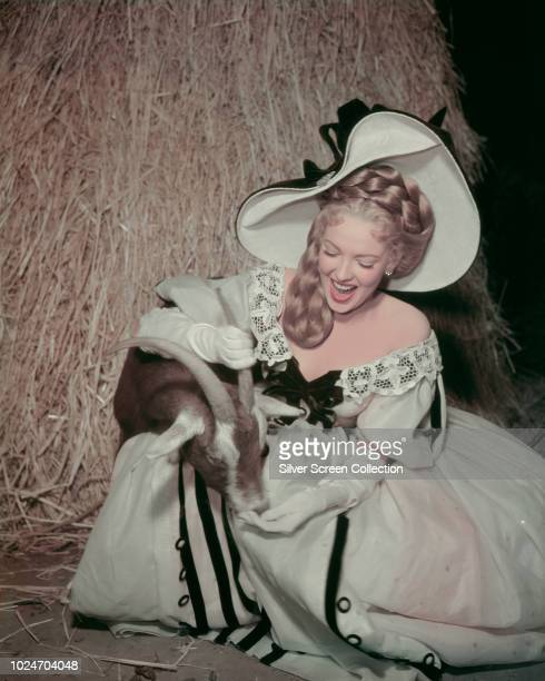 American actress Linda Darnell feeding a goat in a publicity still for the film 'Forever Amber' 1947