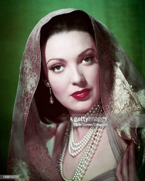 American actress Linda Darnell wearing a headscarf and three pearl necklaces circa 1950