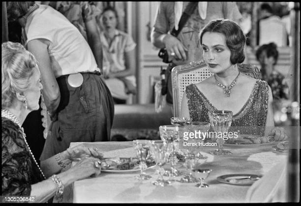 American actress Lois Chiles, a former fashion model, pictured on the film set of Death on the Nile looking across the table at her co-star Bette...