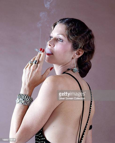 American actress Lois Chiles wearing a backless dress and smoking a cigarette in a promotional portrait for 'Death on the Nile' directed by John...