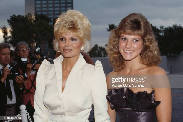 American actress Loni Anderson wearing a white jacket with padded shoulders, and her daughter, Deidre wearing an off-shoulder evening gown, with...