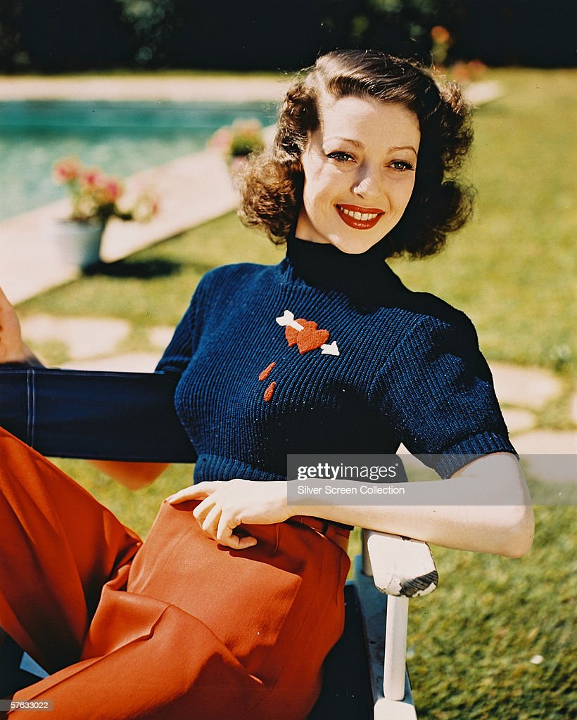American actress Loretta Young (1913 - 2000) relaxes by an outdoor swimming pool, circa 1950. Her jumper carries a motif of two bleeding hearts transfixed by an arrow.