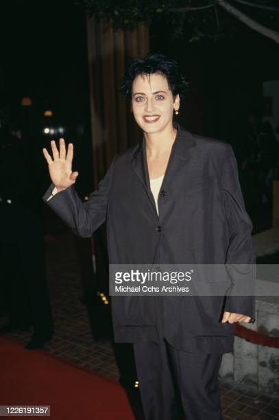American actress Lori Petty wearing a black suit waving as she attends an unspecified event circa 1995