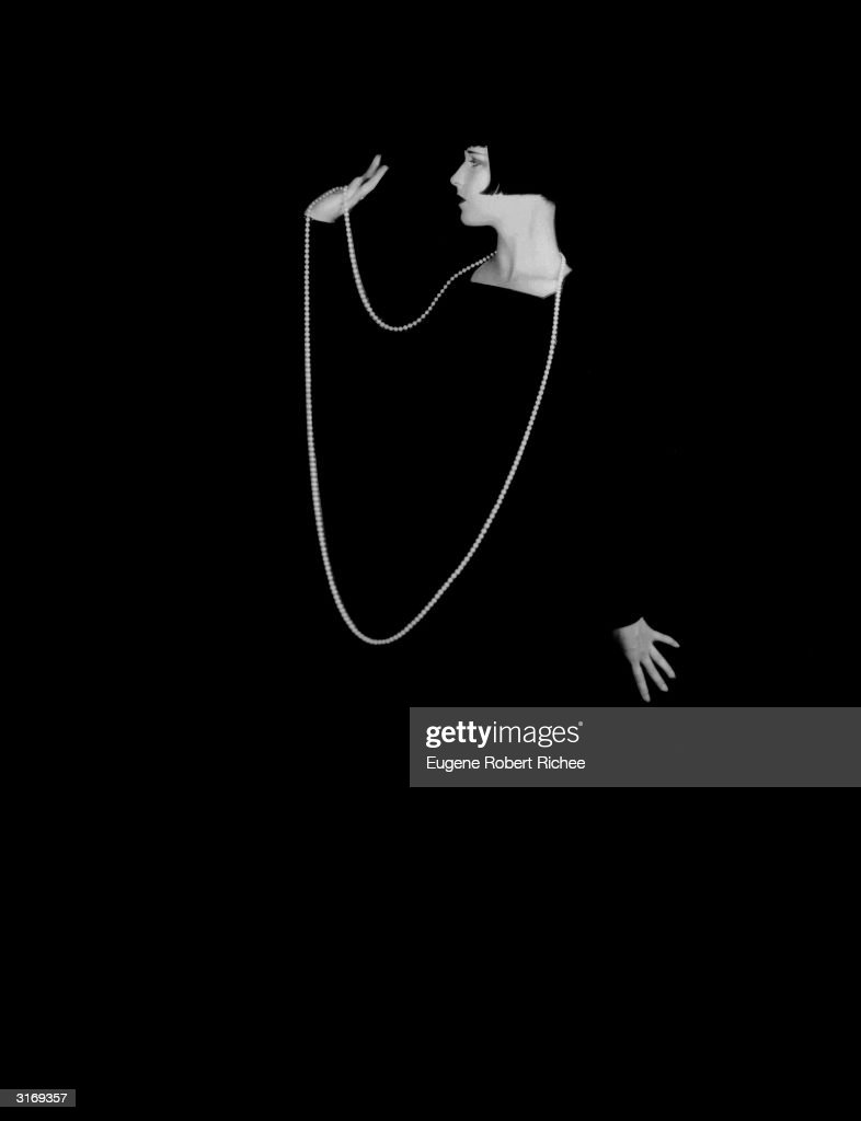 American actress Louise Brooks (1906 - 1985) wearing a long necklace which stands out starkly against a black background.