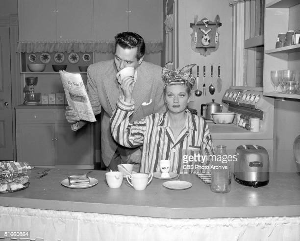 American actress Lucille Ball holds a cup up to her husband, Cuban-born actor Desi Arnaz , as he takes a sip from the cup and reads a newspaper in an...