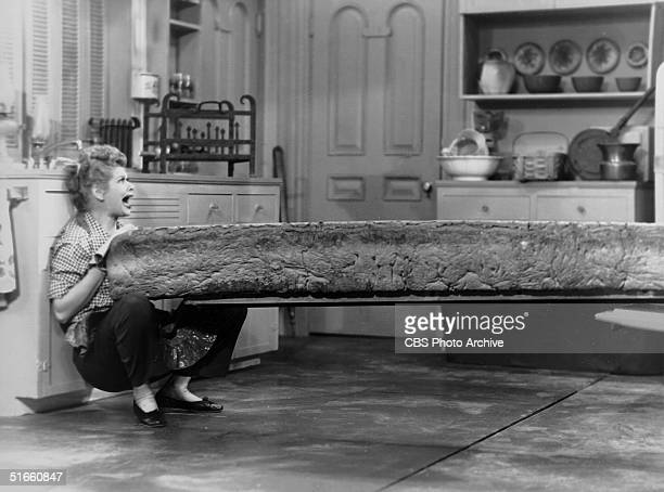 American actress Lucille Ball screams as she is pinned against the kitchen sink during a battle with a giant loaf of bread in a scene from the...
